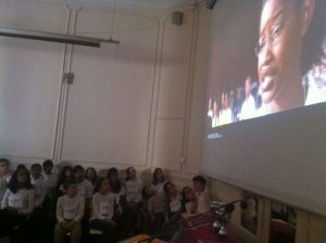 Spellers in the 2013 Paris Spelling Bee competition watch a video clip from the movie Akeelah and the Bee, followed by a surprise video message from Dr. Jacques Bailly, the official pronouncer for the Scripps National Spelling Bee in the US